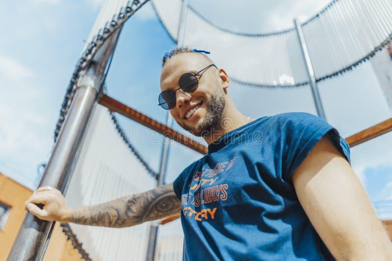 Νέο μοντέρνο άτομο με τα μπλε dreadlocks που χαμογελούν και που στέκονται δίπλα στο αντικείμενο τέχνης στοκ φωτογραφία με δικαίωμα ελεύθερης χρήσης