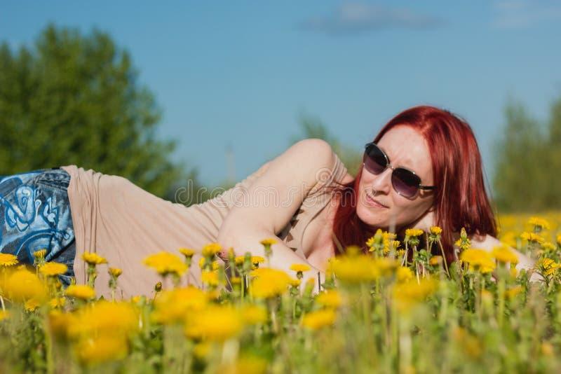 Νέο μοντέρνο ελκυστικό προκλητικό κορίτσι στα γυαλιά που βρίσκονται σε ένα Marguerite-λιβάδι στην ηλιόλουστη θερινή ημέρα στοκ εικόνα