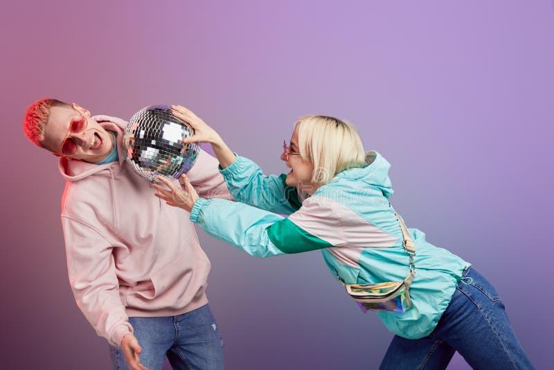 Νέο μοντέρνο ζεύγος των χορευτών που θέτουν με τη σφαίρα disco στο ιώδες υπόβαθρο στοκ φωτογραφίες