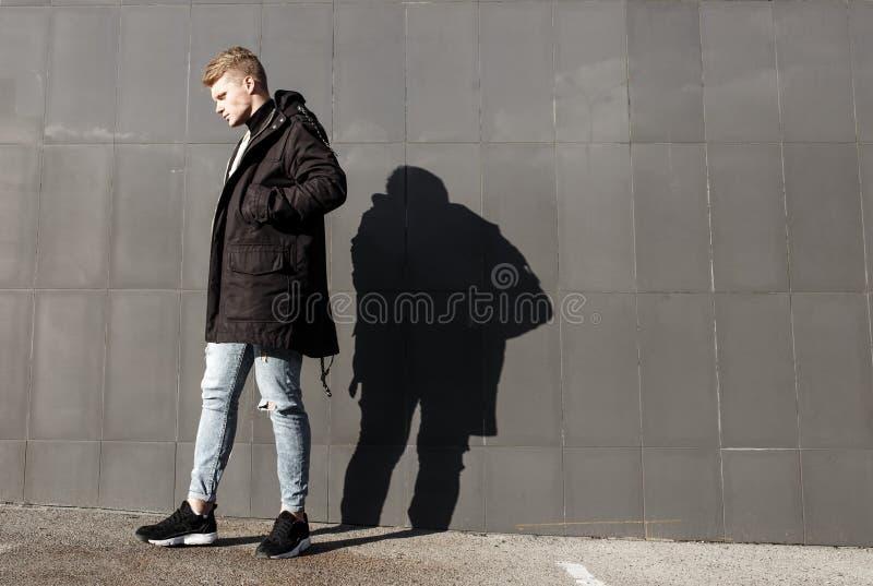 Νέο μοντέρνο redhead άτομο στην καθιερώνουσα τη μόδα τοποθέτηση εξαρτήσεων στο αστικό κλίμα στοκ εικόνες