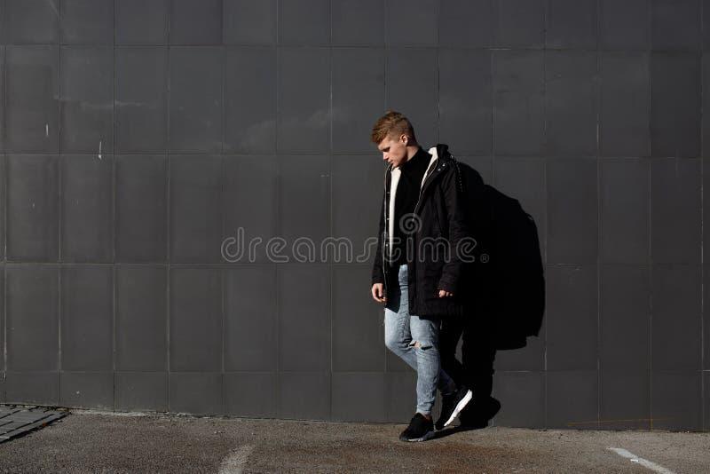 Νέο μοντέρνο redhead άτομο στην καθιερώνουσα τη μόδα τοποθέτηση εξαρτήσεων στο αστικό κλίμα στοκ εικόνα