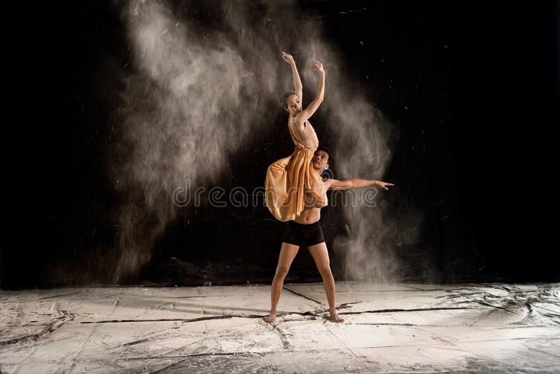 Νέο μπαλέτο ζευγών που χορεύει με τη σκόνη στη σκηνή στοκ εικόνα με δικαίωμα ελεύθερης χρήσης