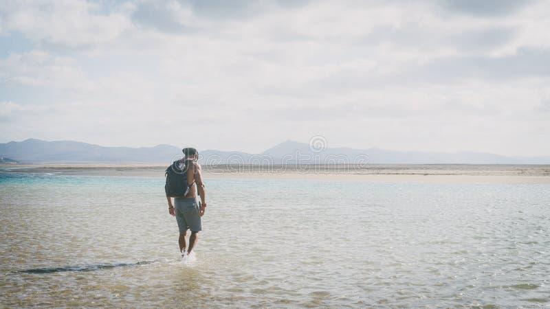 Νέο μυϊκό γενειοφόρο άτομο που περπατά στην ακροθαλασσιά στην ανατολή με το σακίδιο πλάτης ευρέως στοκ φωτογραφία