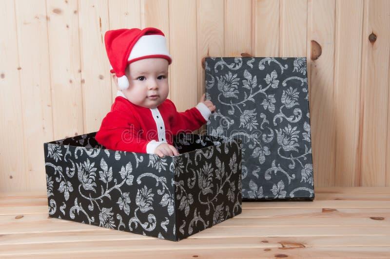 Νέο μωρό που φορά ένα κοστούμι και ένα καπέλο Άγιου Βασίλη στα Χριστούγεννα σε μια σιταποθήκη στοκ φωτογραφία με δικαίωμα ελεύθερης χρήσης