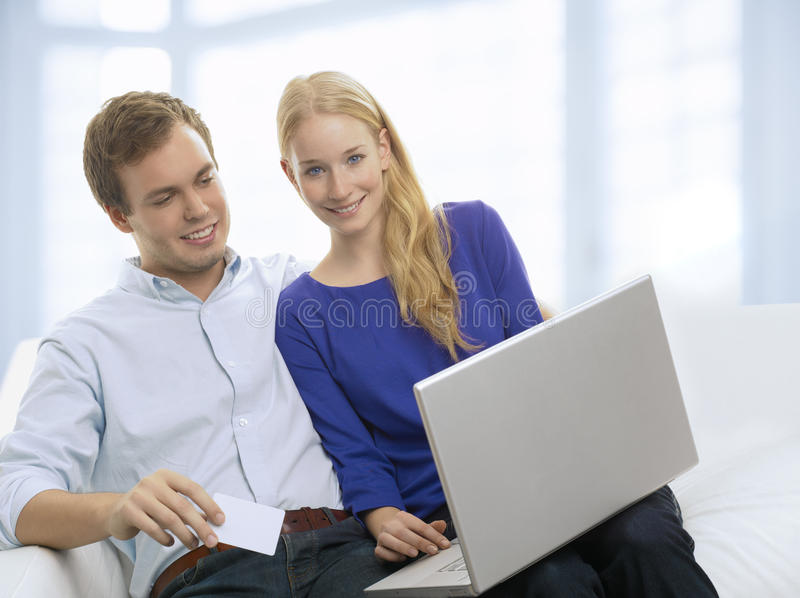 Νέο ζεύγος που ψωνίζει σε Διαδίκτυο με την πιστωτική κάρτα στοκ εικόνα