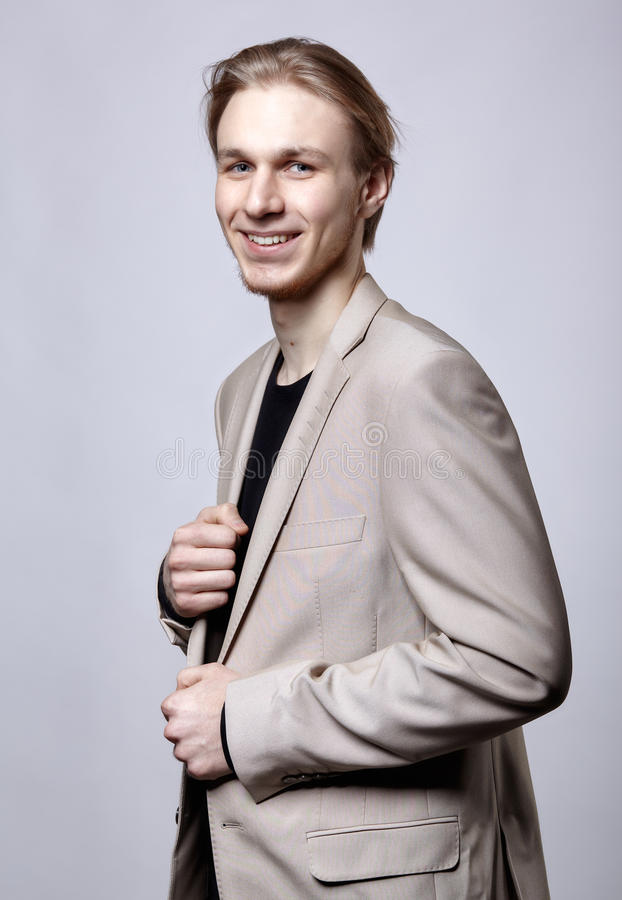 Νέο ξανθό αρσενικό πρότυπο στο μπεζ κοστούμι ατόμων στοκ φωτογραφία