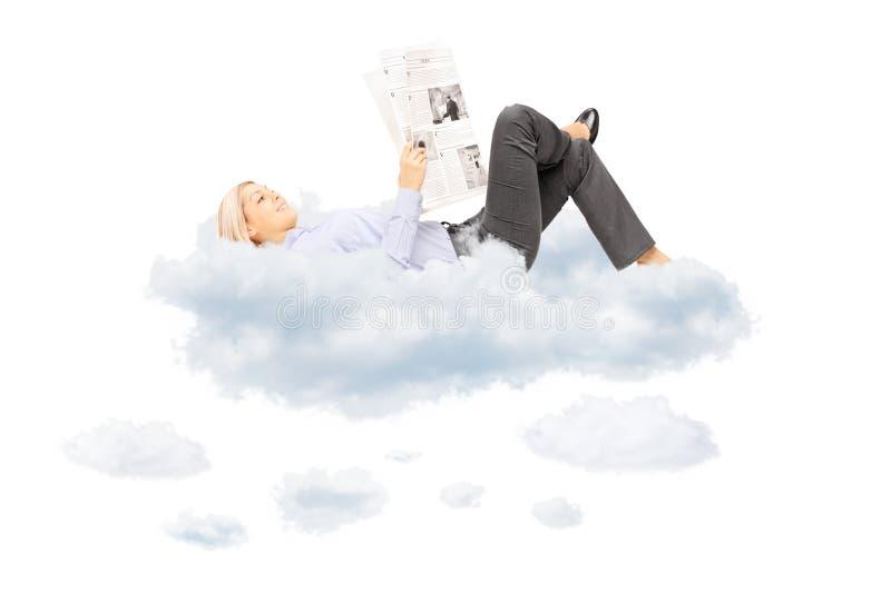 Νέο ξανθό θηλυκό που διαβάζει μια εφημερίδα και που βρίσκεται στα σύννεφα στοκ φωτογραφία