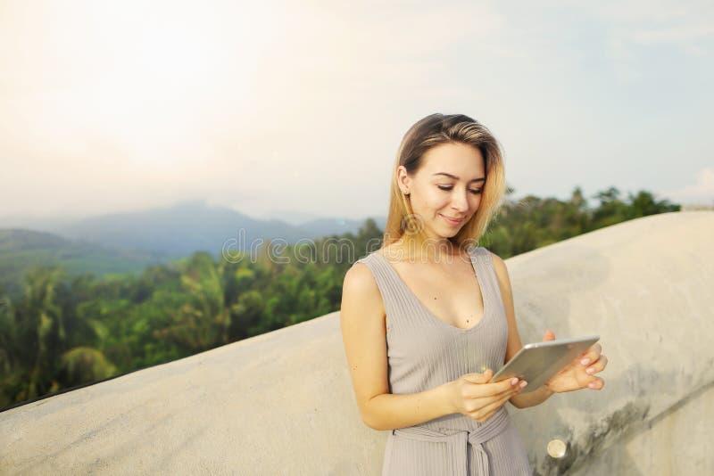 Νέο ξανθό κορίτσι που χρησιμοποιεί την ταμπλέτα με το υπόβαθρο βουνών, Ταϊλάνδη στοκ εικόνα με δικαίωμα ελεύθερης χρήσης