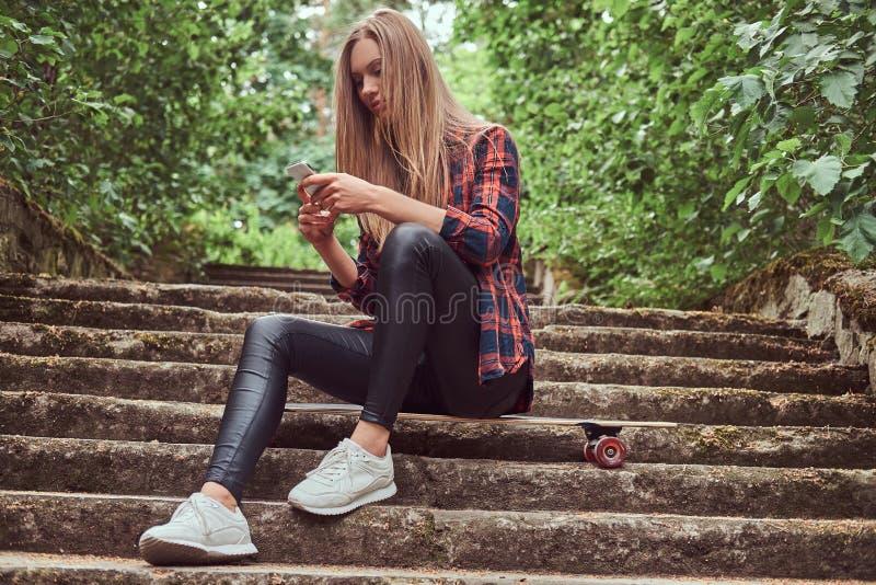 Νέο ξανθό κορίτσι hipster που χρησιμοποιεί ένα smartphone καθμένος στα βήματα σε ένα πάρκο στοκ εικόνες με δικαίωμα ελεύθερης χρήσης