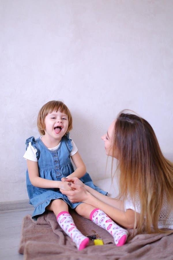 Νέο ξανθό παιχνίδι μητέρων με λίγη κόρη και κάθισμα στο κρεβάτι στοκ εικόνες με δικαίωμα ελεύθερης χρήσης