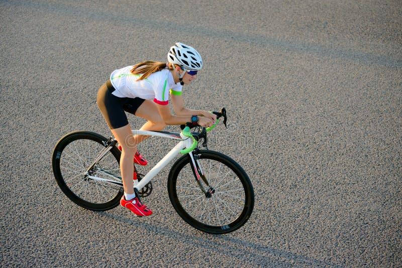 Νέο οδηγώντας οδικό ποδήλατο γυναικών στην ελεύθερη οδό στην πόλη στο ηλιοβασίλεμα Υγιής έννοια τρόπου ζωής και αθλητισμού στοκ εικόνες με δικαίωμα ελεύθερης χρήσης