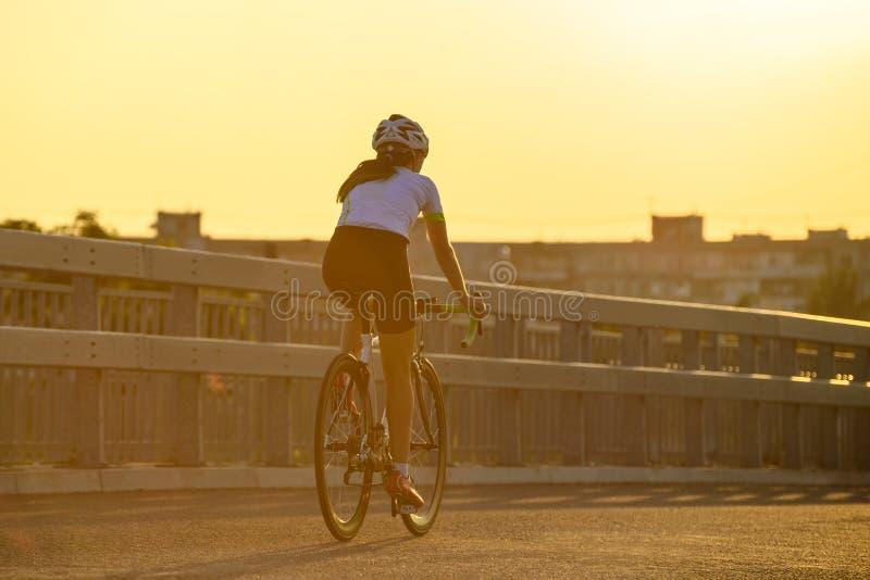 Νέο οδηγώντας οδικό ποδήλατο γυναικών στην ελεύθερη οδό στην πόλη στο ηλιοβασίλεμα Υγιής έννοια τρόπου ζωής και αθλητισμού στοκ εικόνα με δικαίωμα ελεύθερης χρήσης
