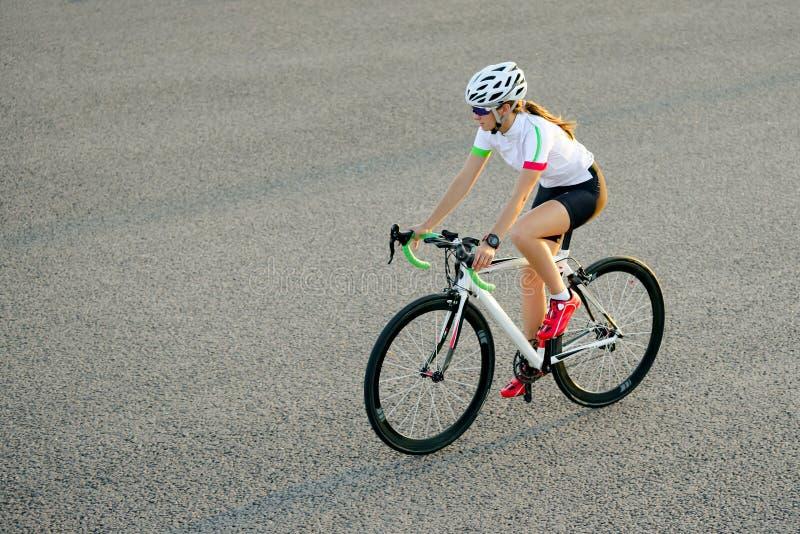 Νέο οδηγώντας οδικό ποδήλατο γυναικών στην ελεύθερη οδό στην πόλη στο ηλιοβασίλεμα Υγιής έννοια τρόπου ζωής και αθλητισμού στοκ φωτογραφία με δικαίωμα ελεύθερης χρήσης