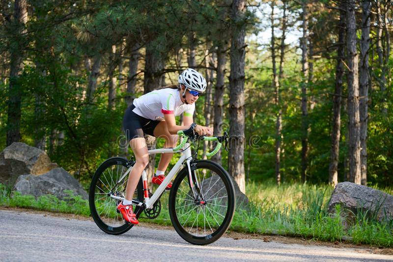 Νέο οδηγώντας οδικό ποδήλατο ποδηλατών γυναικών στον ελεύθερο δρόμο στο δάσος στην καυτή θερινή ημέρα r στοκ εικόνες