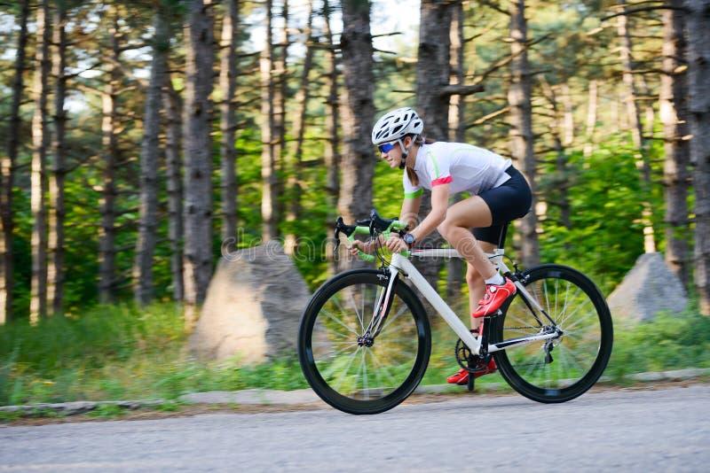 Νέο οδηγώντας οδικό ποδήλατο ποδηλατών γυναικών στον ελεύθερο δρόμο στο δάσος στην καυτή θερινή ημέρα r στοκ φωτογραφίες