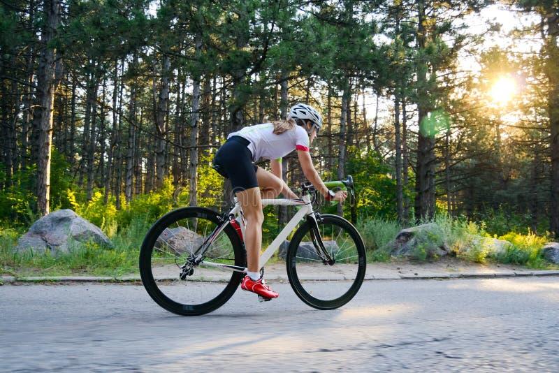 Νέο οδηγώντας οδικό ποδήλατο ποδηλατών γυναικών στον ελεύθερο δρόμο στο δάσος στην καυτή θερινή ημέρα r στοκ φωτογραφίες με δικαίωμα ελεύθερης χρήσης