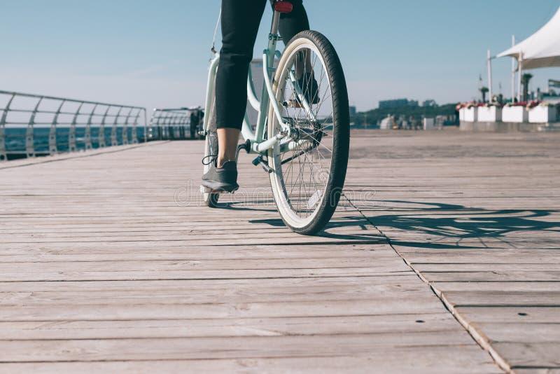 Νέο οδηγώντας ποδήλατο γυναικών στην προκυμαία κοντά στη θάλασσα στοκ φωτογραφίες με δικαίωμα ελεύθερης χρήσης