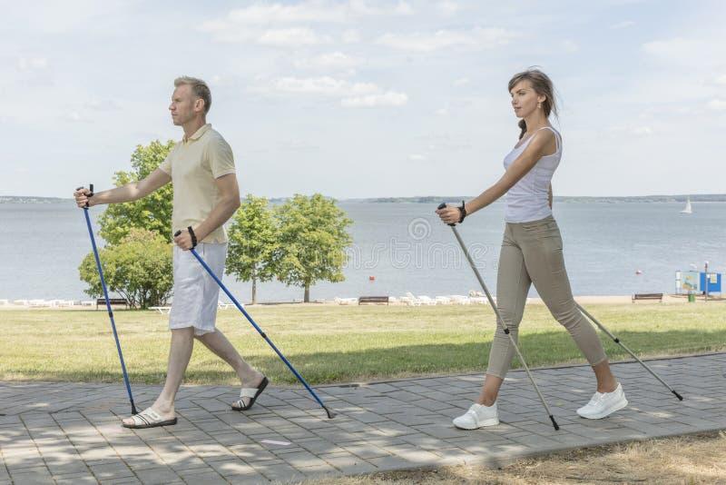 Νέο οικογενειακό ζεύγος που στο σκανδιναβικό περπάτημα φύσης στοκ εικόνες με δικαίωμα ελεύθερης χρήσης