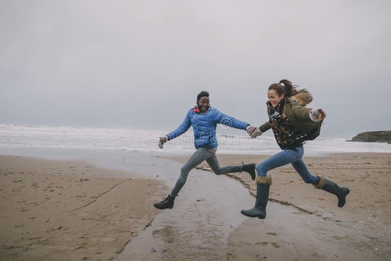 Νέο πήδημα ζεύγους κατά μήκος μιας χειμερινής παραλίας στοκ εικόνες