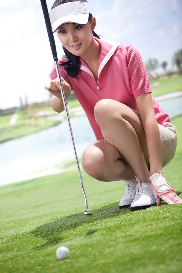 Νέο παίζοντας γκολφ γυναικών στοκ φωτογραφία