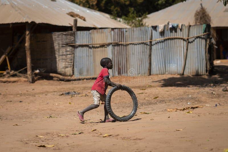 Νέο παιχνίδι αγοριών με μια παλαιά ρόδα, στο χωριό Mandina Mandinga στην περιο στοκ εικόνες