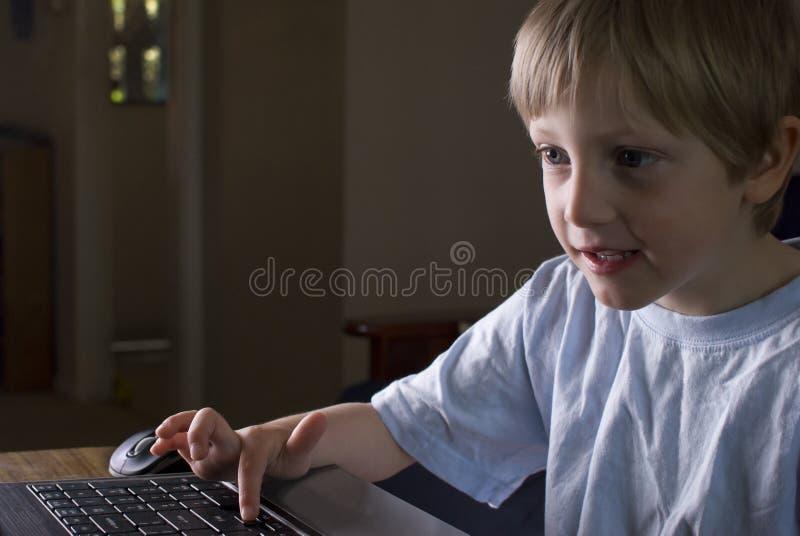 Νέο παιχνίδι αγοριών σε ένα lap-top στοκ φωτογραφία