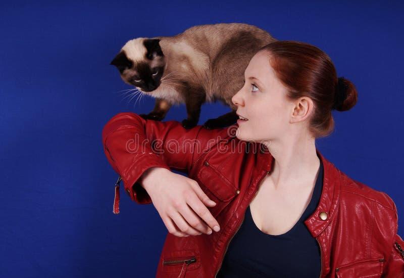 Νέο παιχνίδι γυναικών με τη γάτα στο βραχίονά της στοκ φωτογραφία
