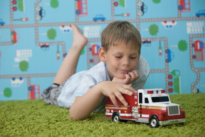 Νέο παιχνίδι αγοριών με το αυτοκίνητο στον τάπητα στοκ εικόνες