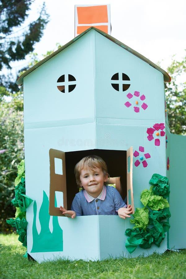 Νέο παιχνίδι αγοριών στο κατ' οίκον γίνοντα σπίτι χαρτονιού στοκ εικόνα