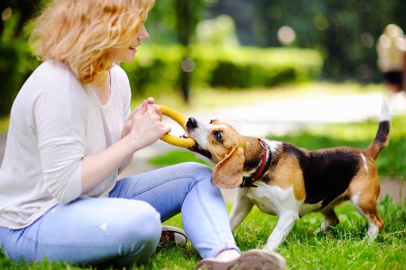 Νέο παιχνίδι γυναικών με το σκυλί λαγωνικών στοκ εικόνα με δικαίωμα ελεύθερης χρήσης