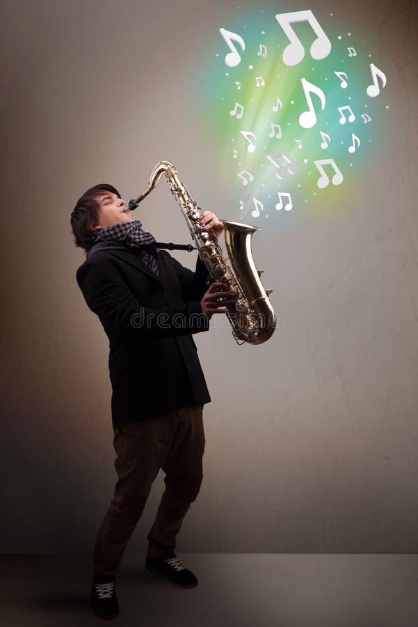 Νέο παιχνίδι μουσικών στο saxophone ενώ μουσικές νότες explodin στοκ φωτογραφία