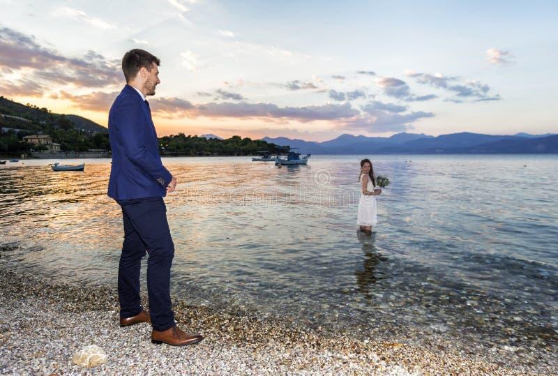 Νέο παντρεμένο ζευγάρι σε έναν seacoast περίπατο στοκ εικόνες