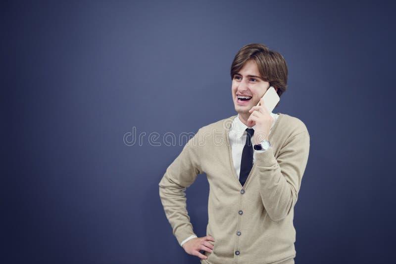 Νέο περιστασιακό άτομο που μιλά στο τηλέφωνο που απομονώνεται στο άσπρο υπόβαθρο στοκ εικόνα