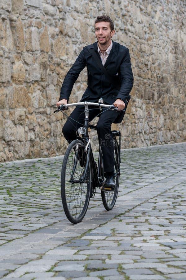 Νέο περιστασιακό επιχειρησιακό άτομο που οδηγά το ποδήλατό του στοκ φωτογραφίες