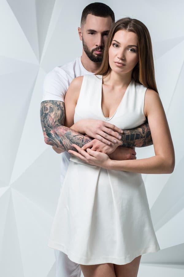 Νέο περιστασιακό ζεύγος με τη γυναίκα που κρατά τα χέρια του πέρα από τον ώμο γυναικών ` s και που ψάχνει τη κάμερα Στην άσπρη αν στοκ φωτογραφία με δικαίωμα ελεύθερης χρήσης