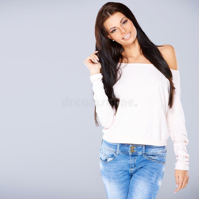 Νέο περιστασιακό κορίτσι που φορά το πουλόβερ και τα τζιν στοκ εικόνες