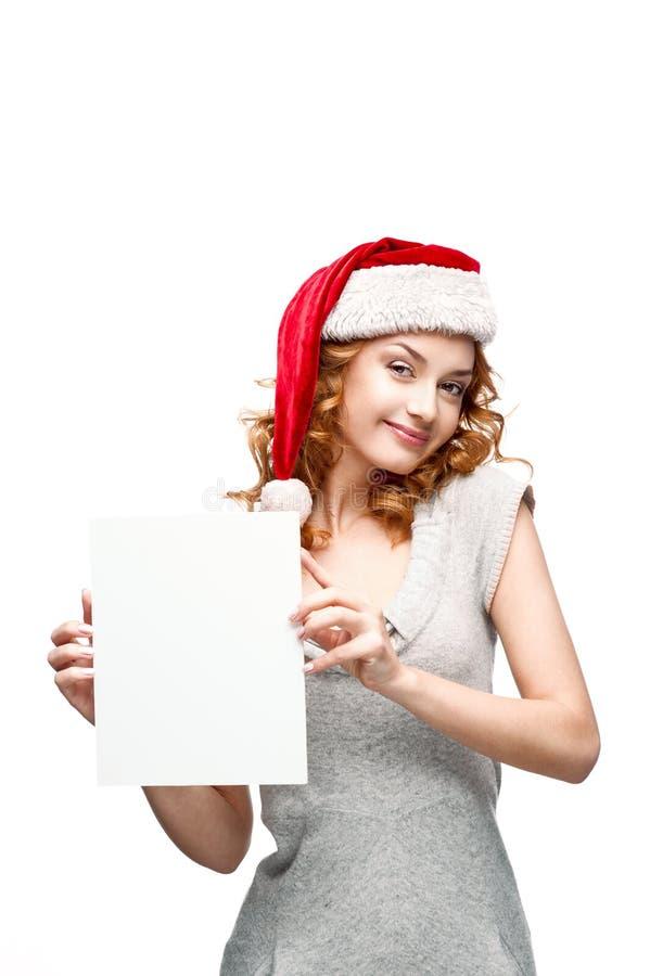Νέο περιστασιακό κορίτσι στο σημάδι εκμετάλλευσης καπέλων santa στοκ εικόνα