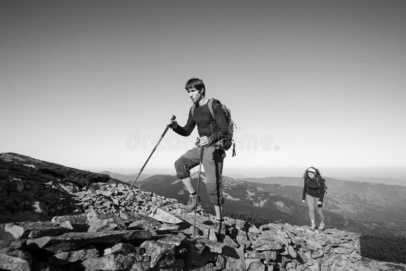 Νέο περπάτημα ζευγών backpacker επάνω δύσκολο η κορυφή βουνών στοκ φωτογραφία με δικαίωμα ελεύθερης χρήσης