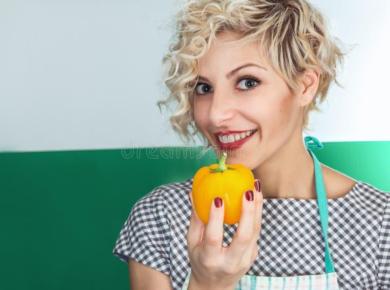 Νέο πιπέρι εκμετάλλευσης μαγείρων γυναικών χαμόγελου στοκ εικόνες