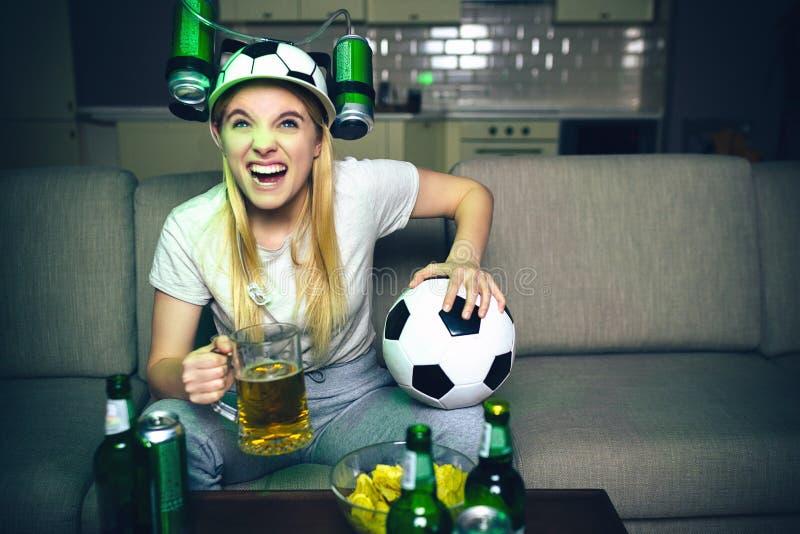 Νέο ποδοσφαιρικό παιχνίδι ρολογιών γυναικών στη TV τη νύχτα Το πρότυπο κάθεται στον καναπέ και το ποτήρι λαβής της μπύρας με τη σ στοκ φωτογραφία