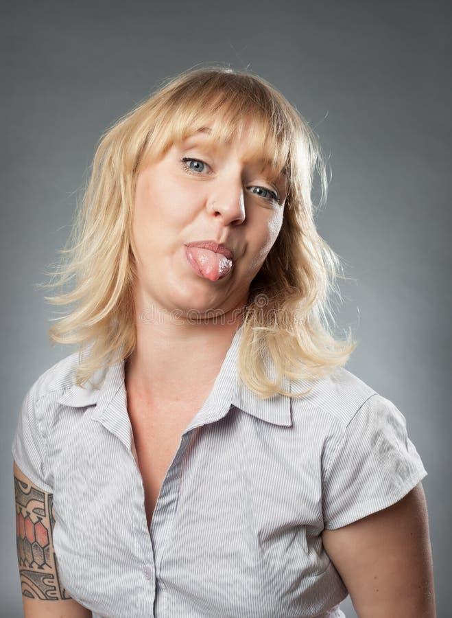 Νέο πορτρέτο γυναικών, που κολλά έξω τη γλώσσα της στοκ φωτογραφία