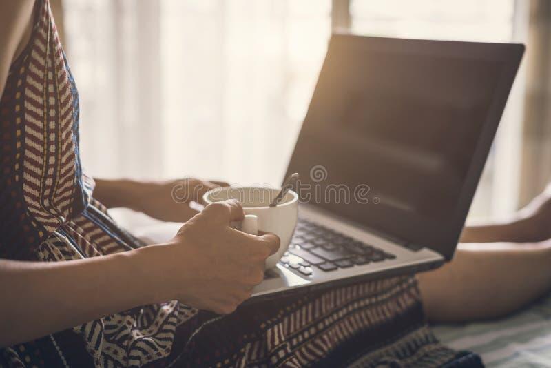 Νέο ποτό γυναικών του καφέ και της χρησιμοποίησης του φορητού προσωπικού υπολογιστή στοκ εικόνα με δικαίωμα ελεύθερης χρήσης