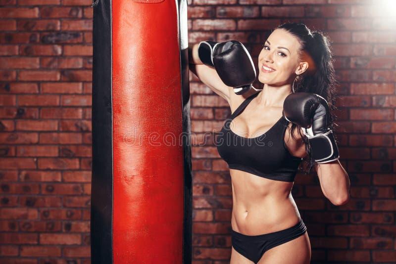 Νέο προκλητικό κορίτσι με τα εγκιβωτίζοντας γάντια, punching τσάντα στοκ εικόνες