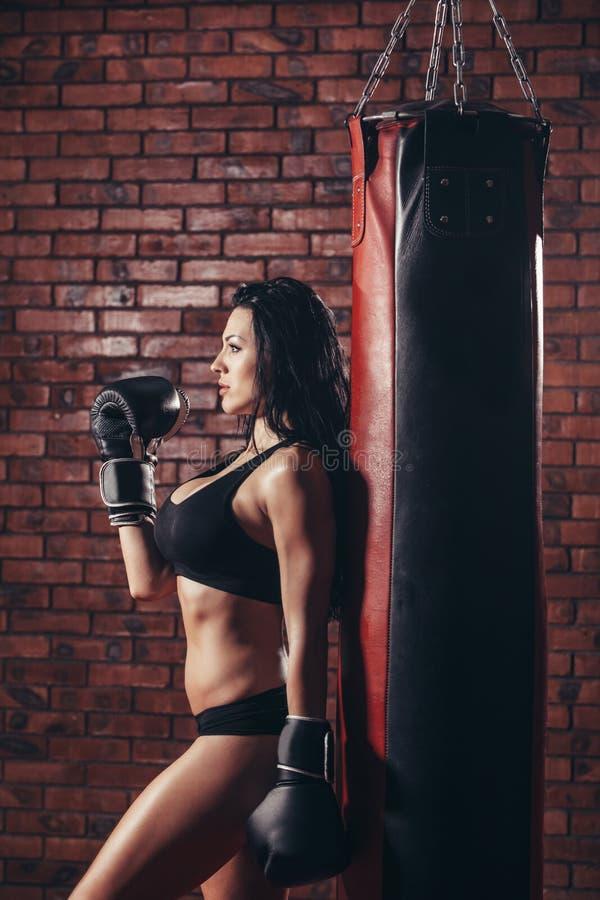 Νέο προκλητικό κορίτσι με τα εγκιβωτίζοντας γάντια, punching τσάντα στοκ φωτογραφία με δικαίωμα ελεύθερης χρήσης