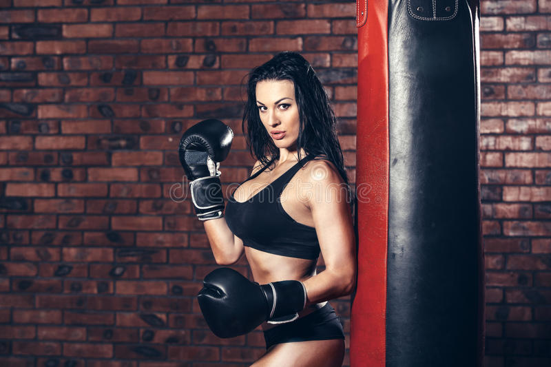 Νέο προκλητικό κορίτσι με τα εγκιβωτίζοντας γάντια, punching τσάντα στοκ φωτογραφίες