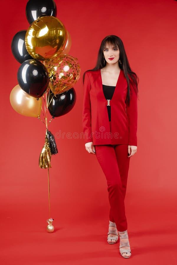 Νέο πρότυπο brunette στην κόκκινη τοποθέτηση κοστουμιών κοντά στα μπαλόνια στοκ εικόνες με δικαίωμα ελεύθερης χρήσης