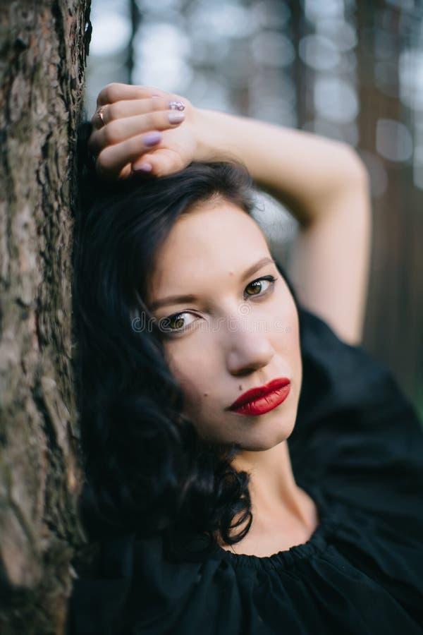 Νέο πρότυπο brunette στην κόκκινη φούστα, το μαύρο σακάκι και τα κόκκινα χείλια στοκ φωτογραφία με δικαίωμα ελεύθερης χρήσης