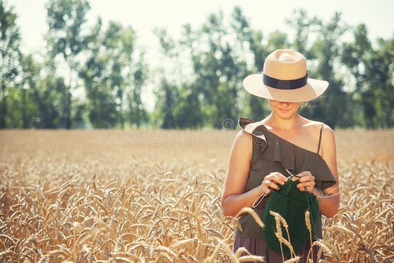 Νέο πλέξιμο γυναικών στον τομέα σίτου στοκ φωτογραφία με δικαίωμα ελεύθερης χρήσης