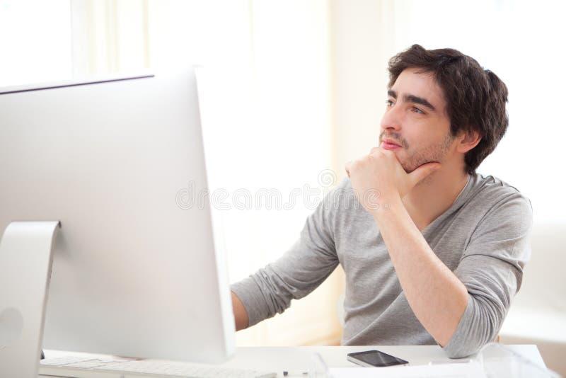 Νέο σκεπτικό άτομο μπροστά από τον υπολογιστή στοκ φωτογραφίες