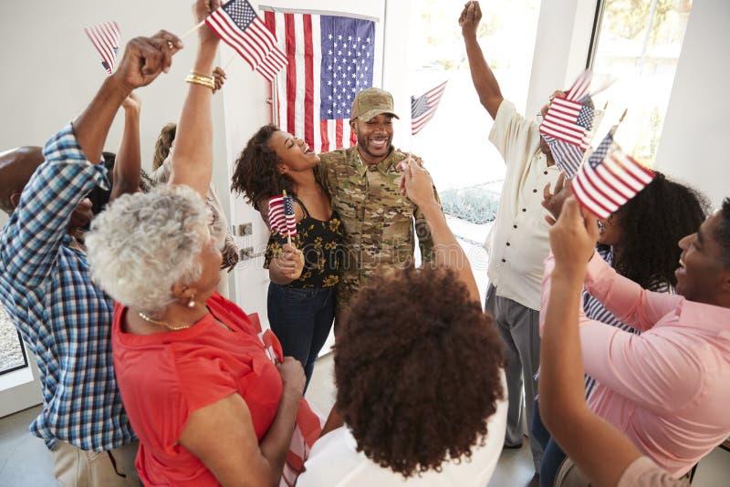 Νέο σπίτι επιστροφής στρατιωτών αφροαμερικάνων αρσενικό στην ενθαρρυντική οικογένειά του, ανυψωμένη άποψη στοκ φωτογραφία